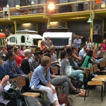 Eine größere Gruppe Menschen sitzt und hört einem Mann zu, der in ein Mikrofon spricht