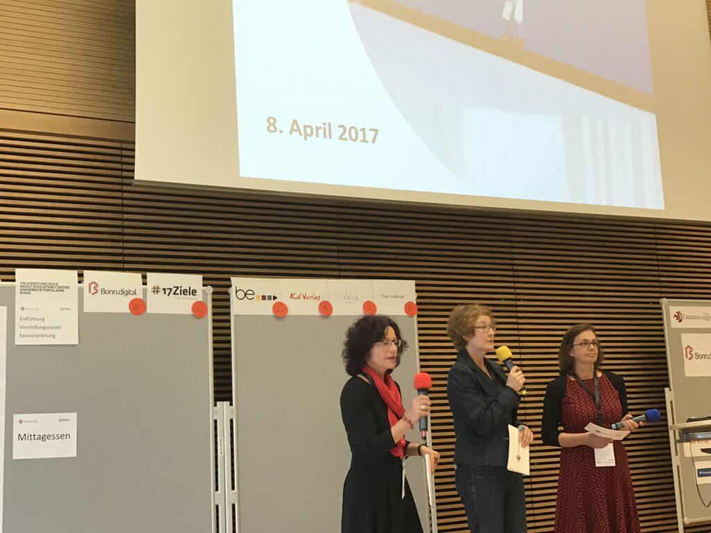 Drei Frauen stehen auf der Bühne, alle halten ein Mikrofon in der Hand, die mittlere (Uschi) spricht hinein