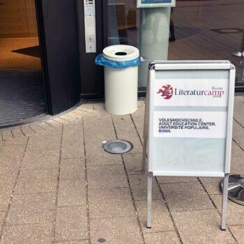 Ein Aufsteller, in dem das Logo des Literaturcamps Bonn sowie der Volkshochschule sind.