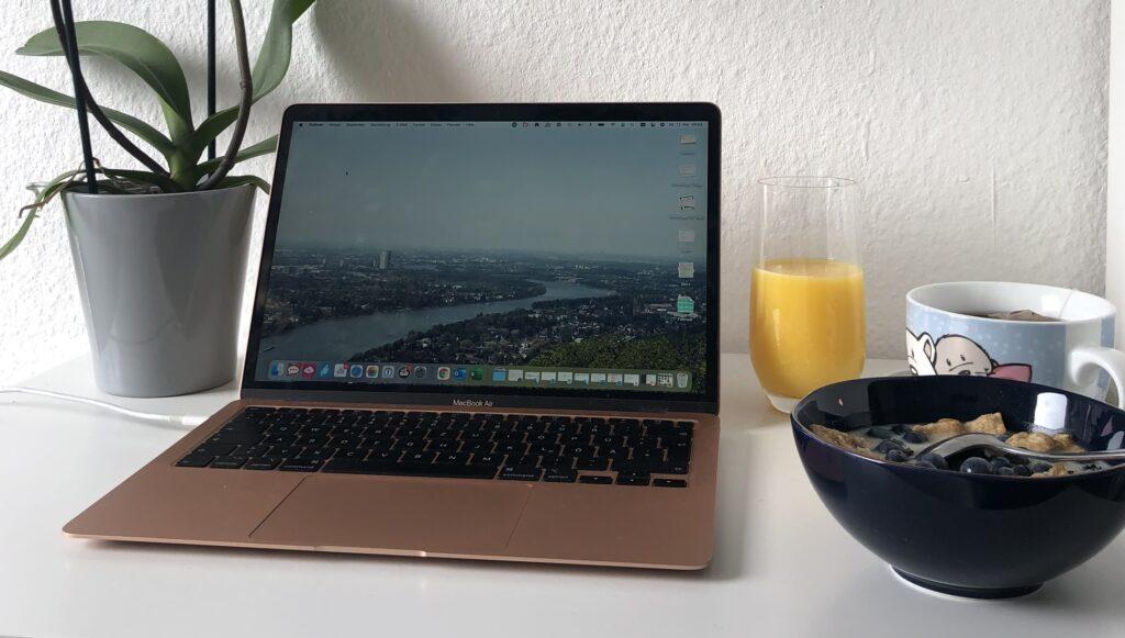 Laptop Orangensaft und Müslischale