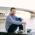 Ein Mann sitzt auf einer Mauer vor dem Rhein, hinter ihm die Kennedybrücke. Er hält einen Leitz-Ordner in der Hand.
